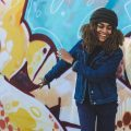 Happy women smiling against painted wall