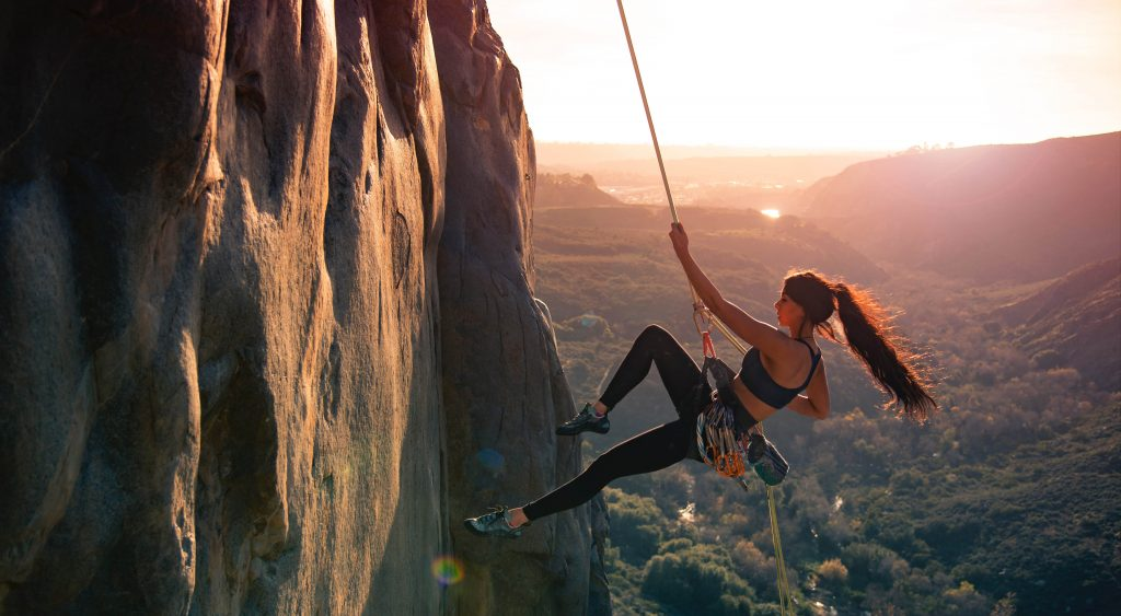 Strong woman abseiling