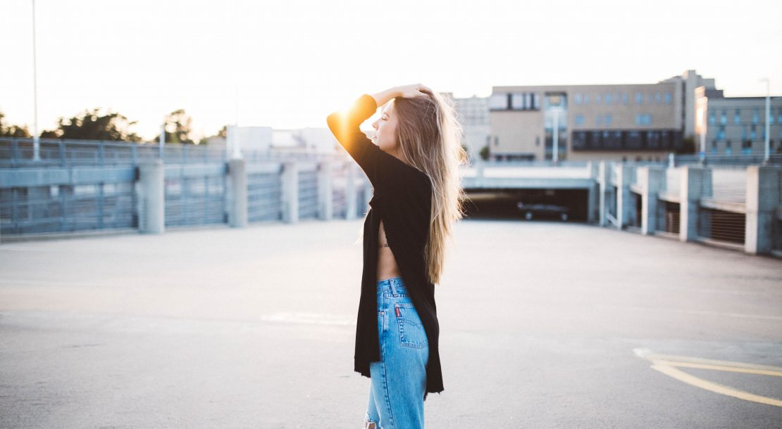 Woman with glowing skin and hair standing in sun