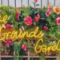 The Grounds of Alexandria neon sign and flowers around window