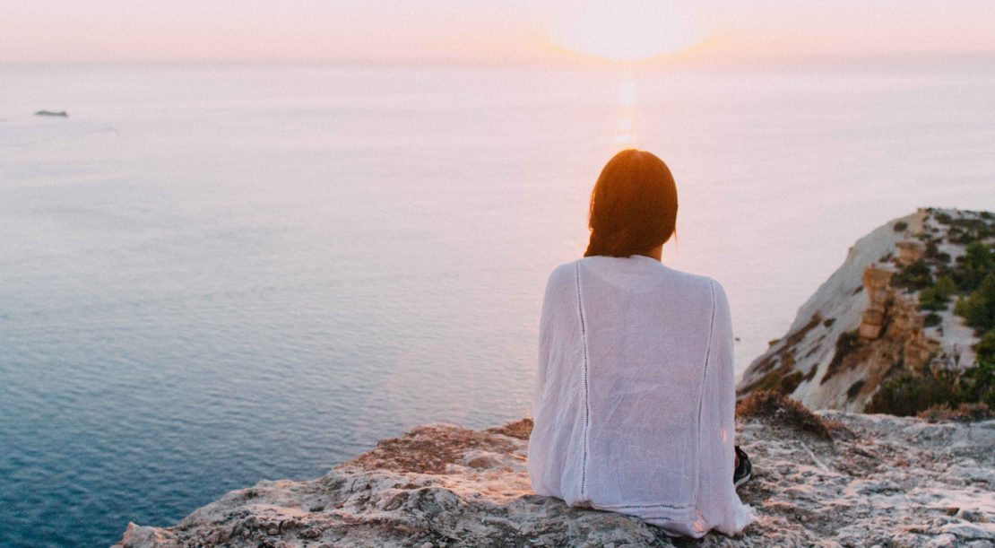 Woman sitting on cliff looking over ocean