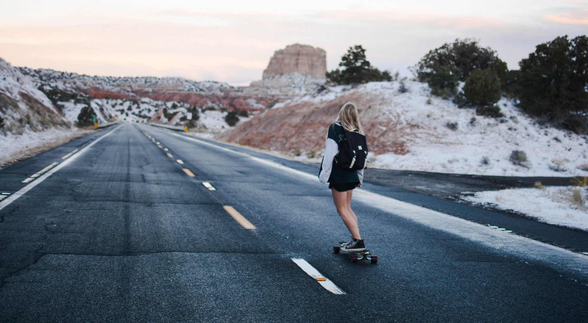 Woman skateboaring down road