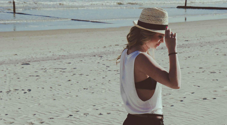 Woman walking on beach wearing hat