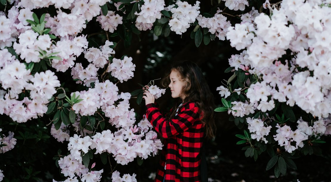 Young girl smelling flowers in garden