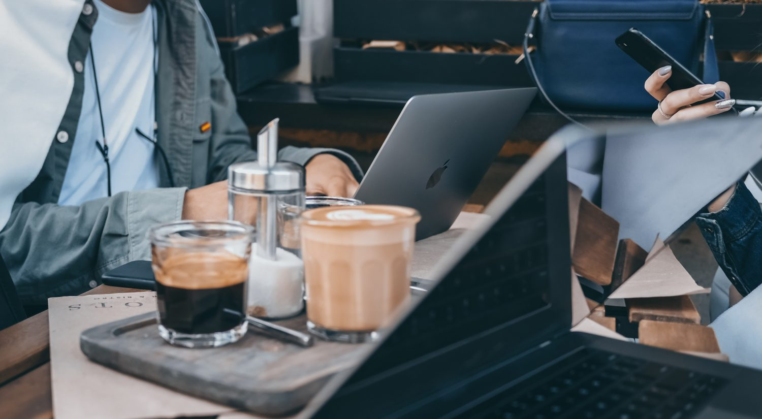 Couple working with laptops at cafe