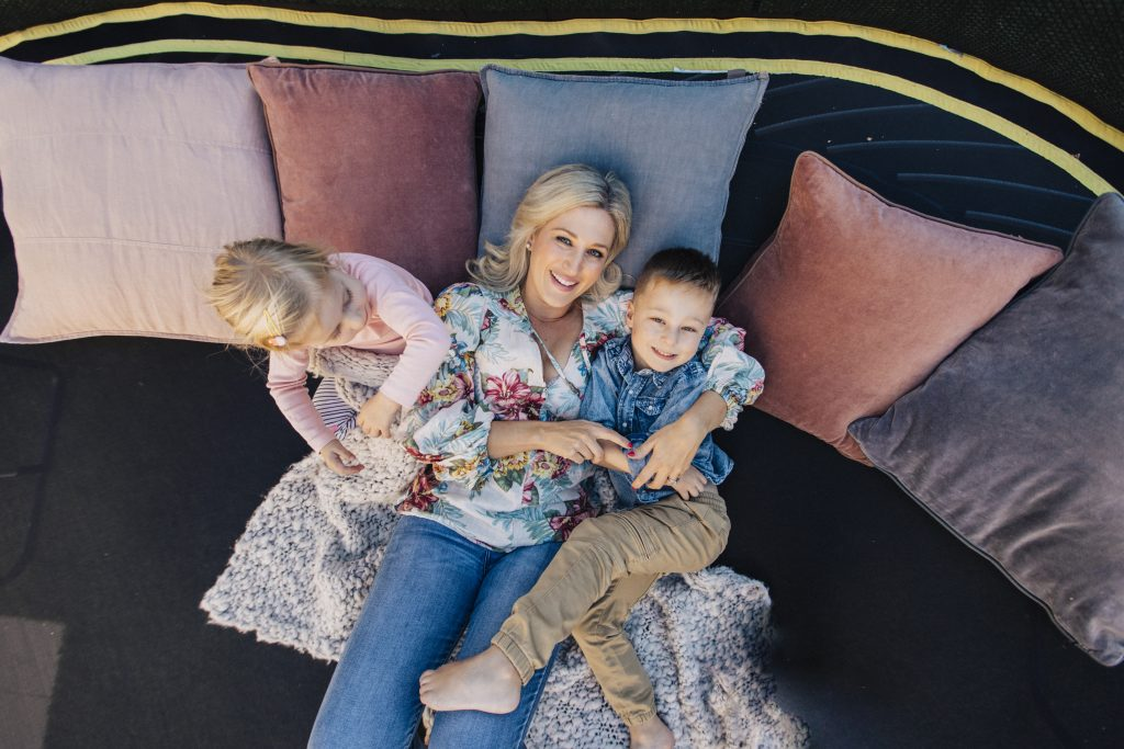 Mum relaxing on trampoline with children