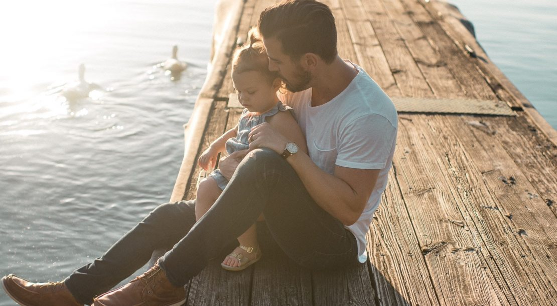Father and daughter sitting on jetty