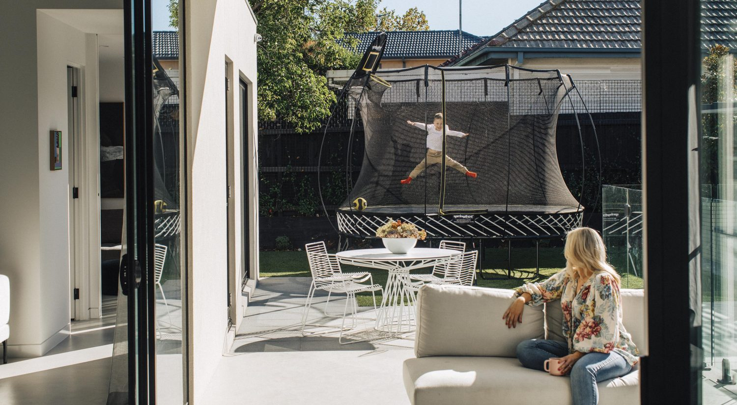 Springfree trampoline set up in backyard with outdoor setting