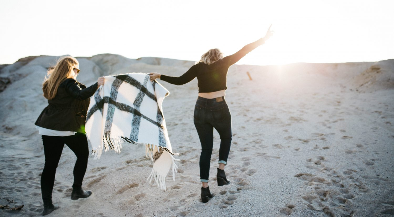 Two women walking and having fun on sand dunes