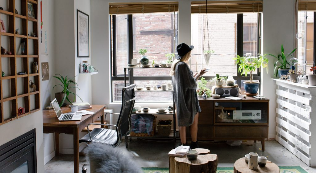 Woman standing in her stylish home office with plants
