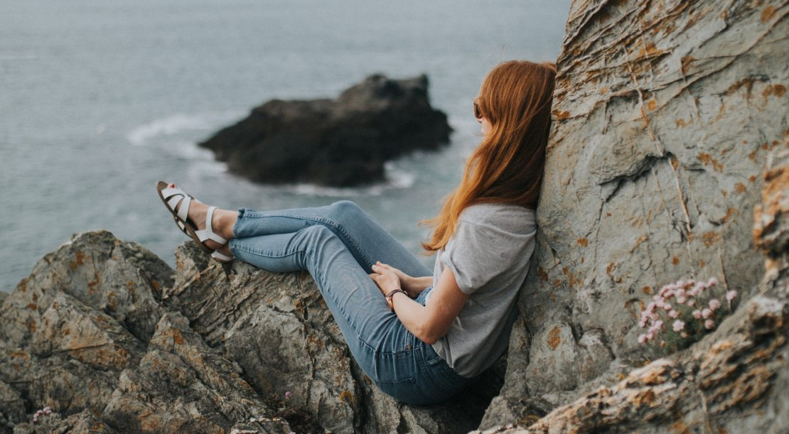 Woman sitting on cliff pondering