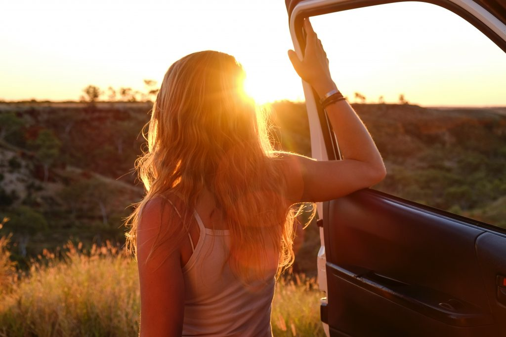 Woman on road trip standing next to car