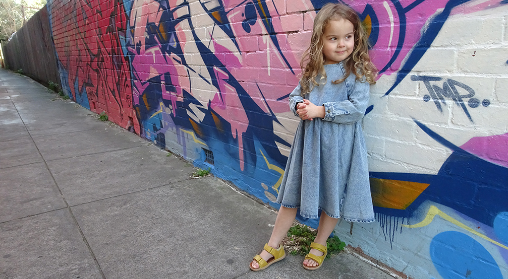 Little girl wearing Bobux shoes standing against wall
