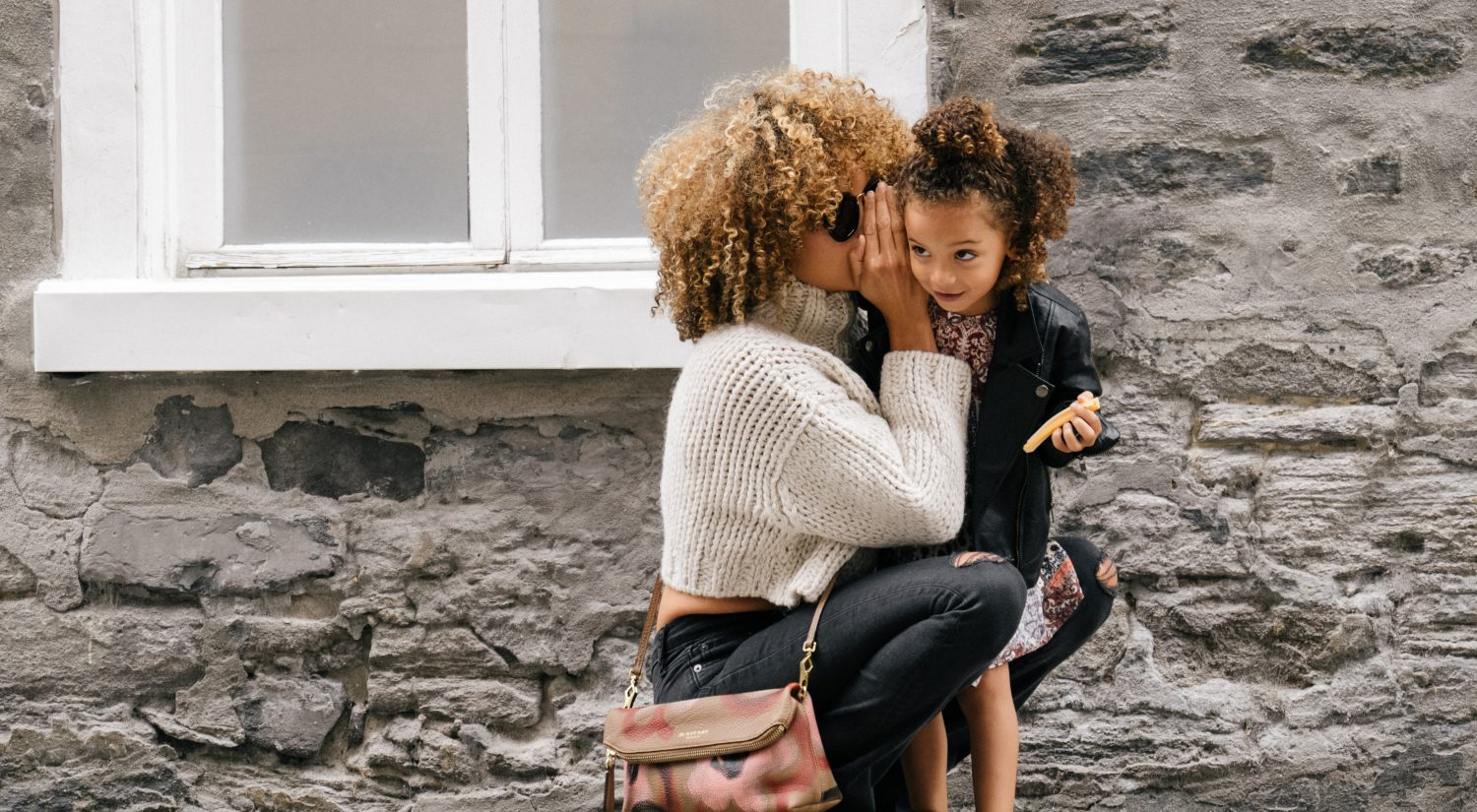 Mother whispering to daughter child