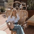 Taylor Sterling sitting on rattan seat outdoors
