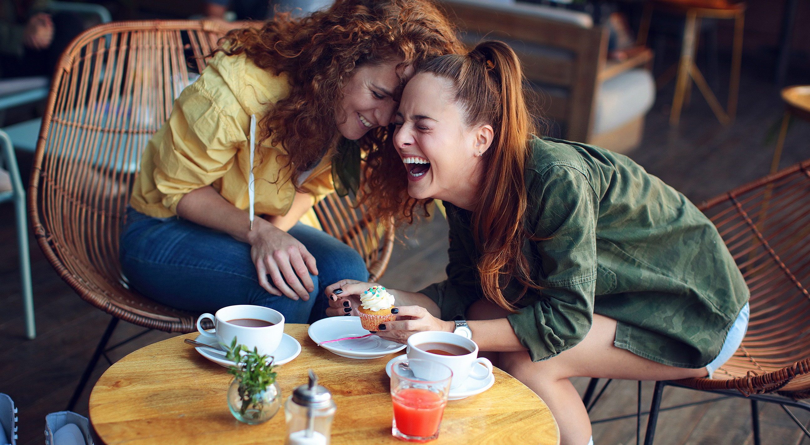 Two women laughing at coffee shop