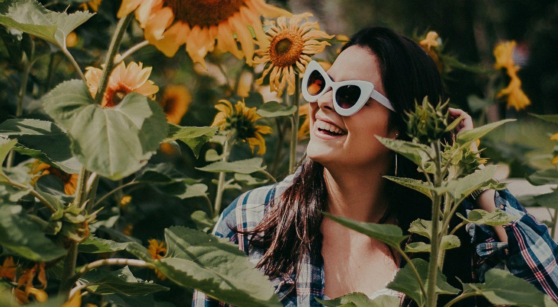 Woman standing amongst sunflowers