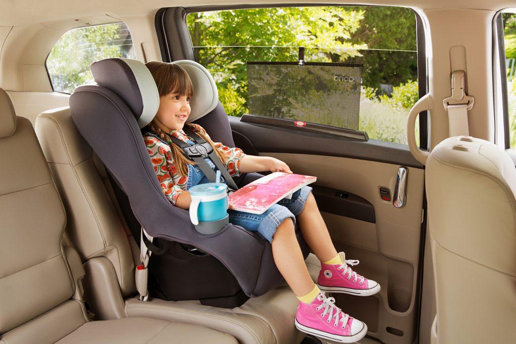 Girl in car seat with Brica by Munchkin sun shade on window