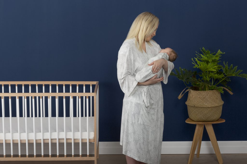 Mum holding baby in nursery weraing ergopouch matchy matchy robe
