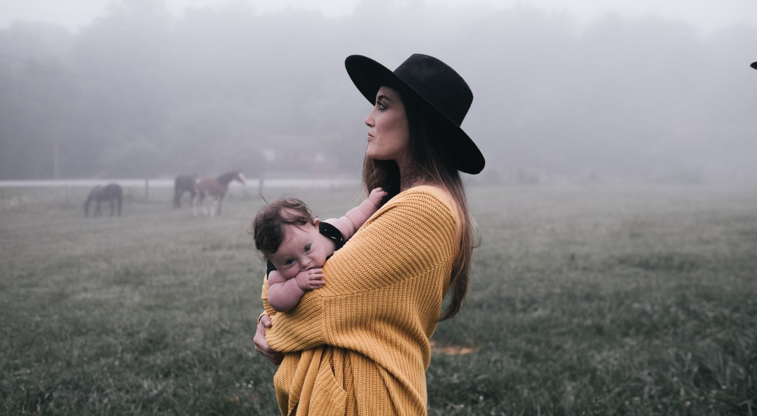 Mum holding baby with horses in background