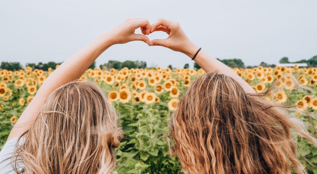 Two girls making love sign with sunflowers in background