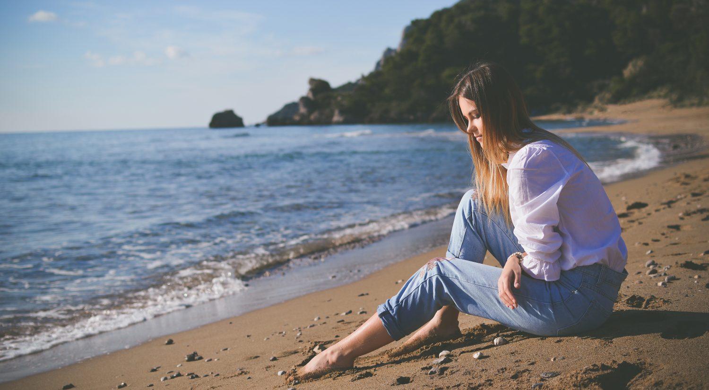 Woman sitting on beach thinking