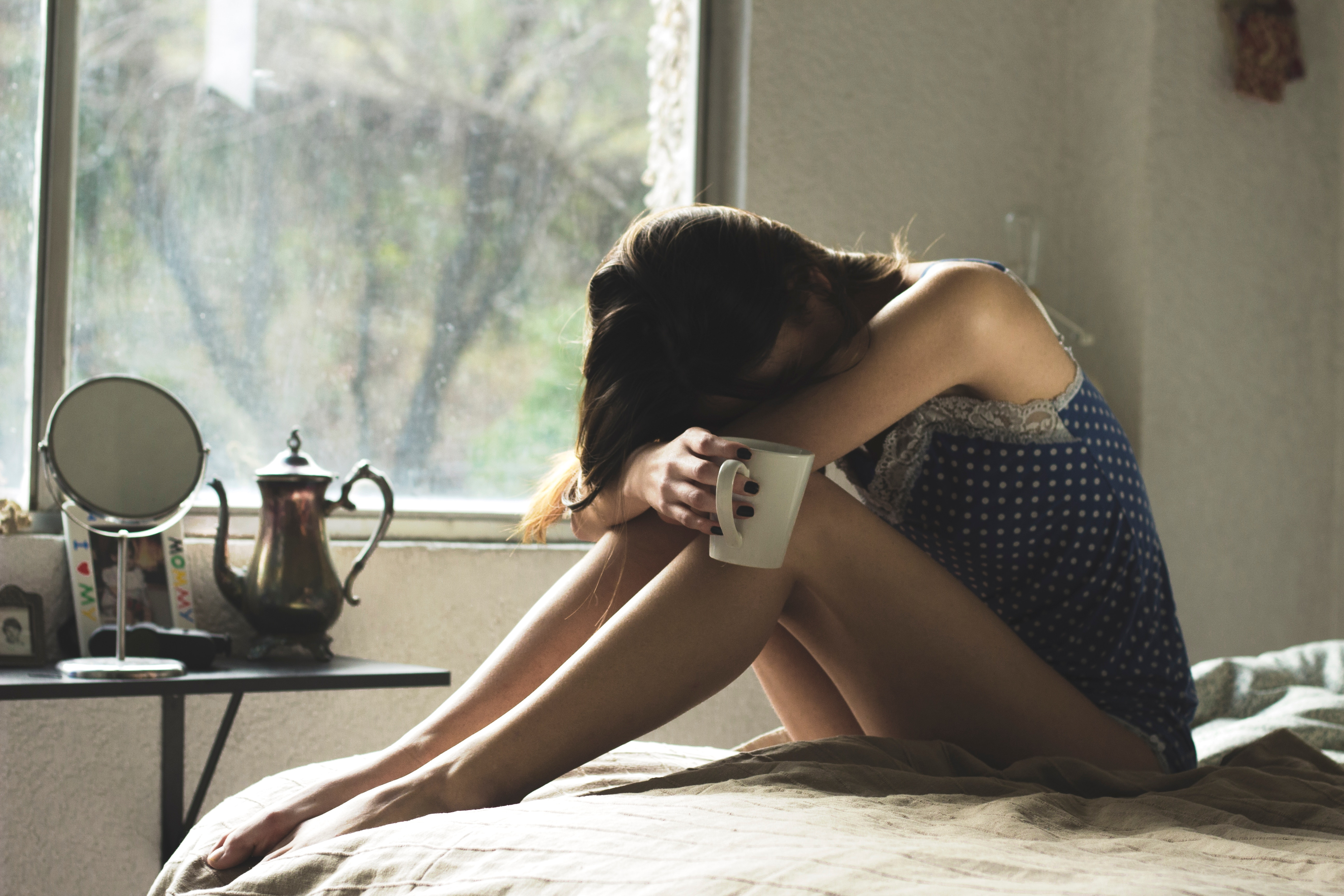 Woman sitting on bed tired with cup of tea