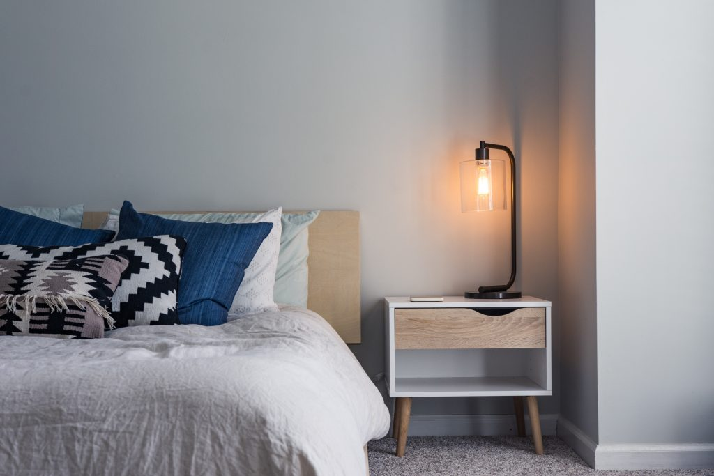Bed with bedside table and lamp