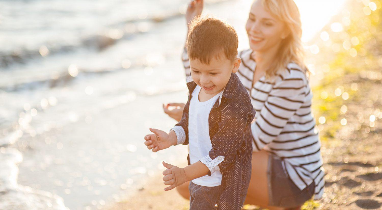 Carer playing with child on beach