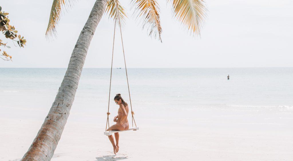 Woman on swing on beach