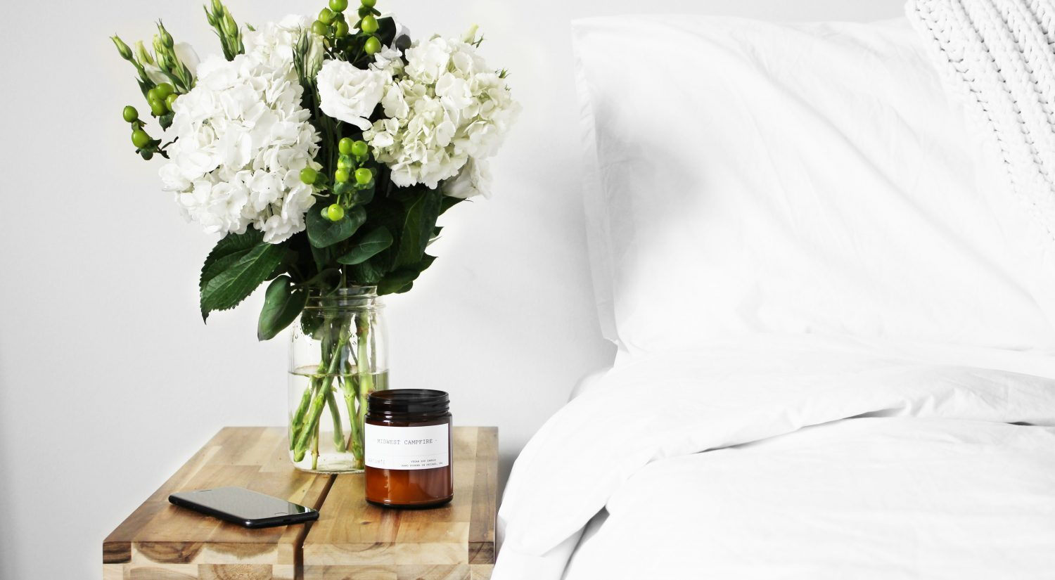White bed with beside table and flowers
