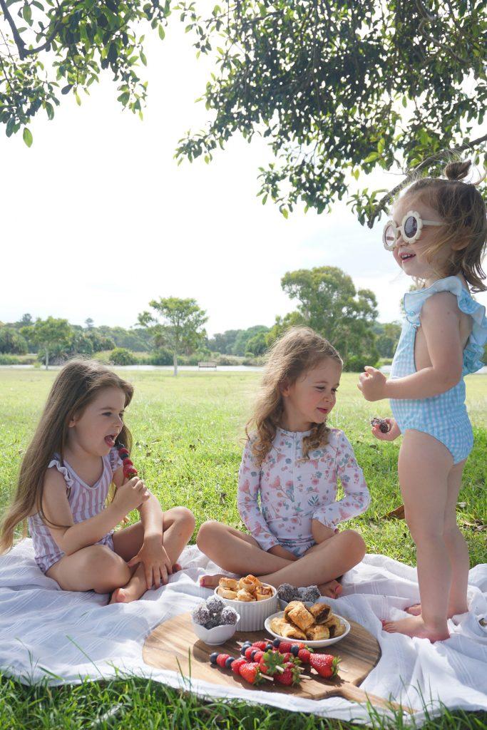 Willow Swim kids eating at picnic wearing swimsuits