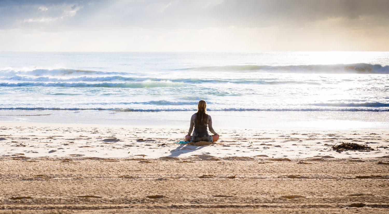 Women doing yoga meditation on beach