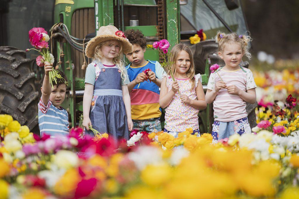 Oishi-m kids standing in field of flowers